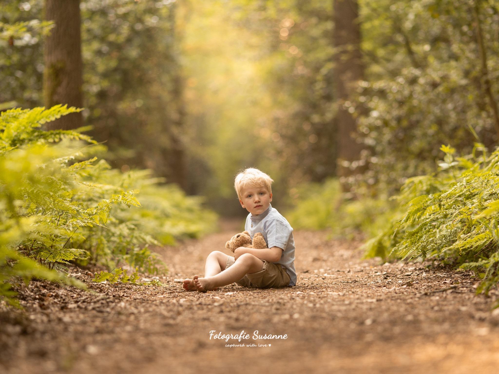 Jongen met beertje in het bos