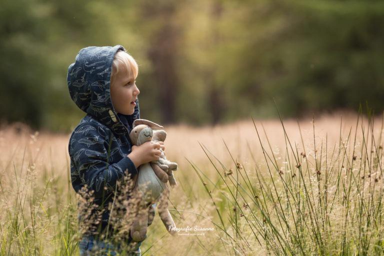 Jongen met knuffel in de natuur